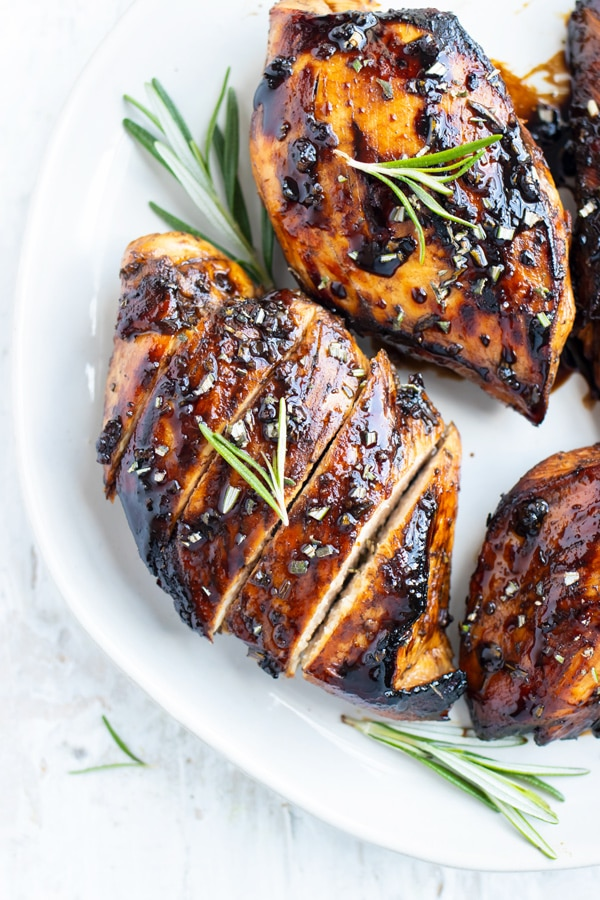 A honey balsamic chicken breast on a white plate with a sprig or rosemary.