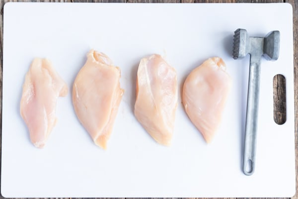 Four organic chicken breasts that have been pounded and tenderized for a recipe.