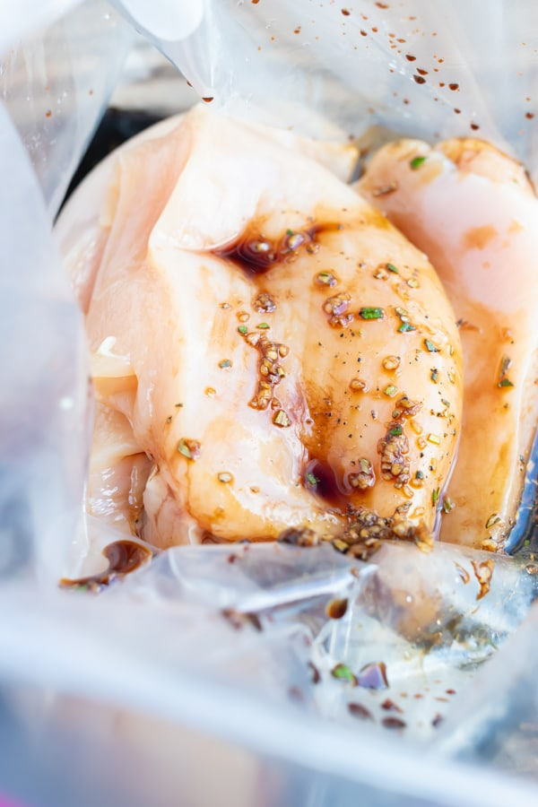 Chicken breasts soaking in a balsamic marinade before cooking.