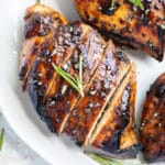 Three balsamic chicken breasts on a white plate with a sprig or rosemary.