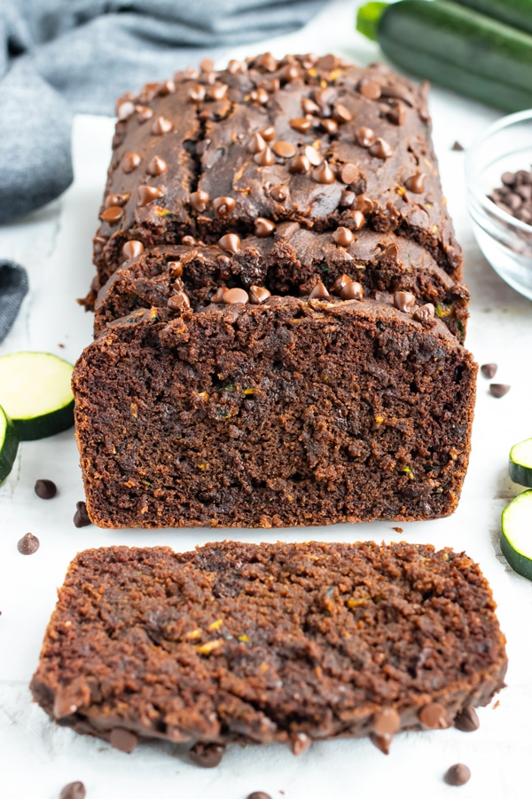 A slice of zucchini bread with chocolate chips on a table next to a grey napkin.