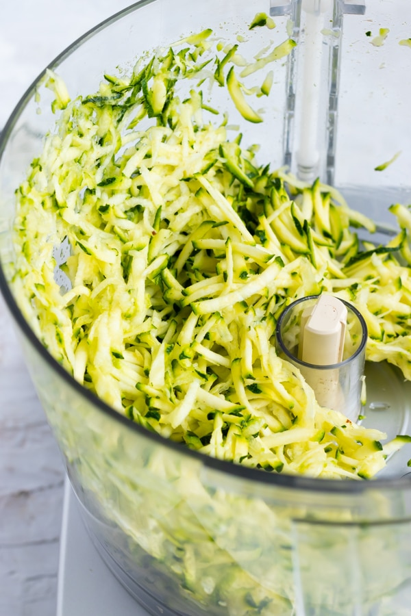 Grated zucchini in a food processor for a zucchini bread recipe.