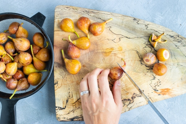 Cutting the stems off of brown turkey figs on a wooden cutting board for a fresh fig recipe.