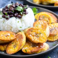 Fried plantains on a plate with rice and beans.