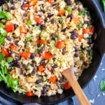 A cast-iron skillet with a gallo pinto recipe in it with a wooden spoon and cilantro.