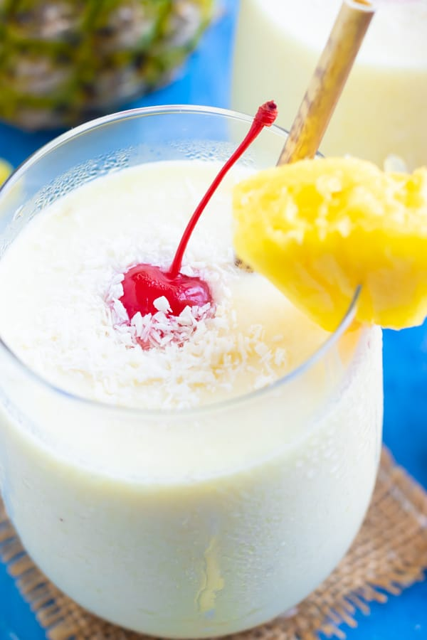 A frozen pina colada recipe in a clear glass with a pineapple wedge and a maraschino cherry.