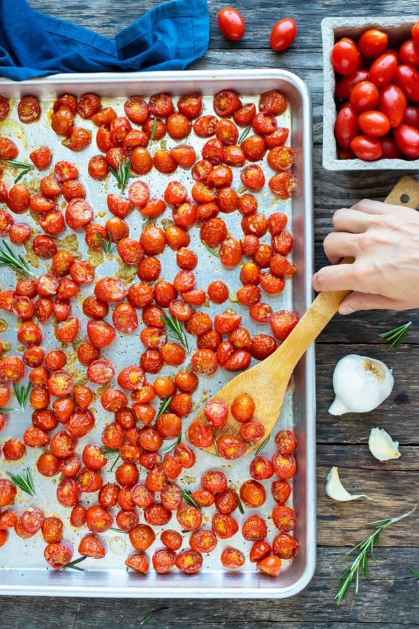 Roasted cherry tomatoes on a large baking sheet with a hand scooping up some.