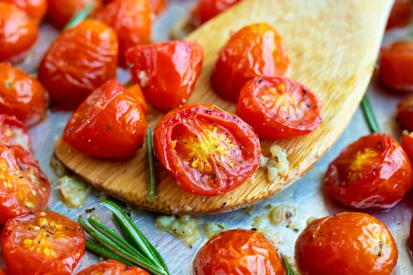 Roasted grape tomatoes on a silver baking sheet with garlic and rosemary.
