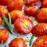 Roasted cherry tomatoes on a baking sheet with rosemary next to it.