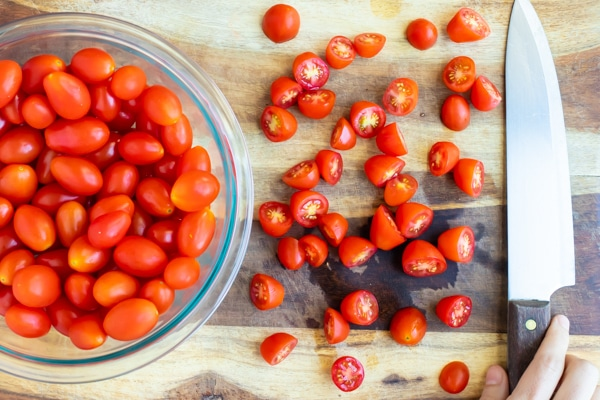 Cherry tomatoes being cut in half on a wooden cutting board.