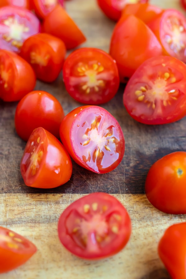 A close-up of grape tomatoes that have been cut in half.