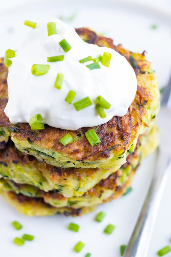 A close-up of sour cream on top of zucchini fritters to serve.