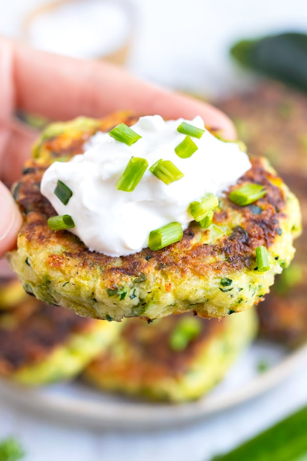 A hand holding a zucchini fritter with sour cream on top and green onions.
