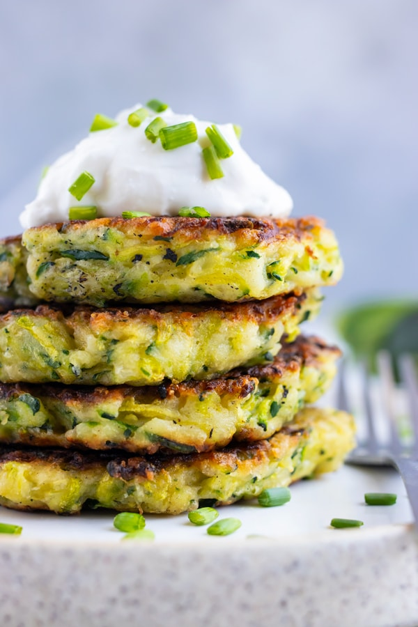 Four zucchini fritters in a stack on a white plate.