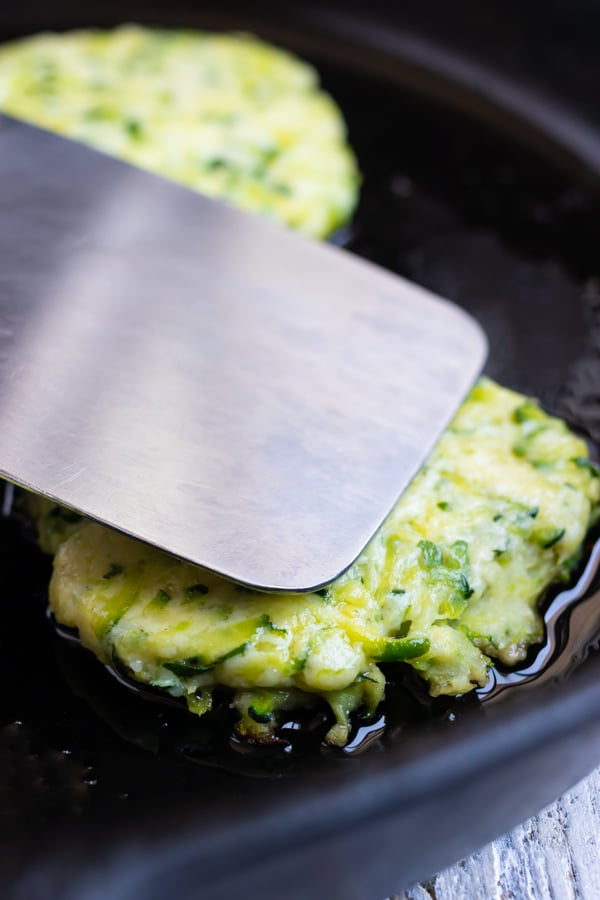 Frying zucchini fritters in a cast-iron skillet.