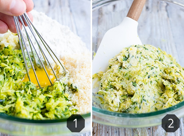 A glass bowl full of zucchini fritters batter that is being mixed together.