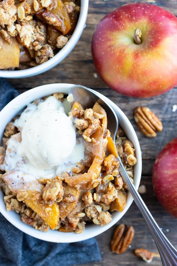 Two dessert bowls full of a gluten-free apple crisp recipe with oats and pecans.