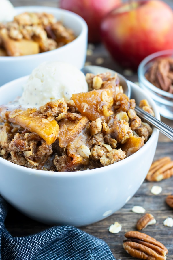 Two dessert bowls full of a gluten-free apple crisp recipe with an oatmeal and pecan crumb topping.