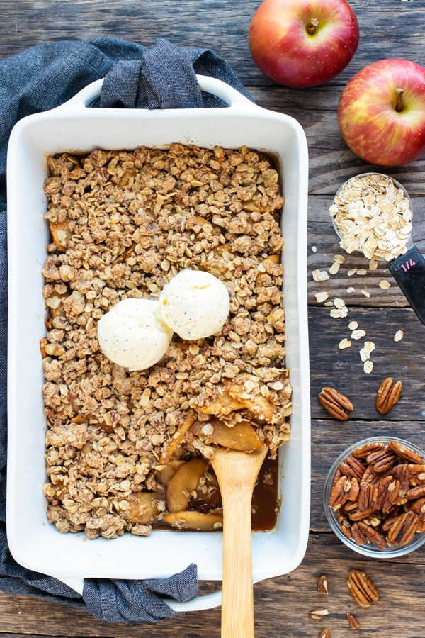 A large white baking dish with a healthy, gluten-free, and the best apple crisp recipe next to oats, two apples, and a bowl of pecans.