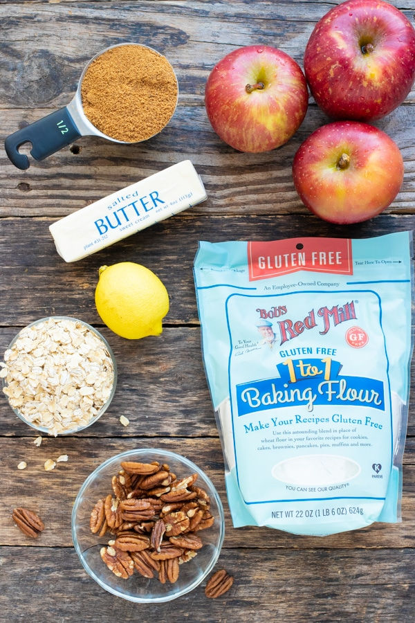 Apples, sugar, butter, oats, pecans, and flour as the ingredients for a gluten-free and vegan apple crisp recipe.