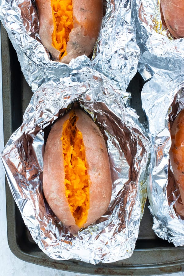Four sweet potatoes that have been baked on a sheet pan in the oven.