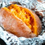 A baked sweet potato wrapped in aluminum foil.