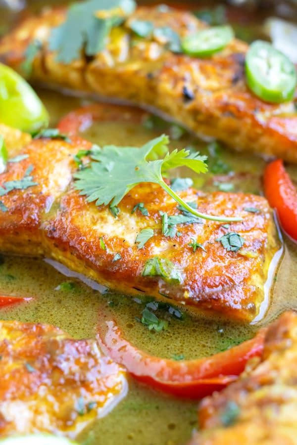 A close-up of a salmon fillet in a coconut milk green curry sauce made with lime juice and curry powder.