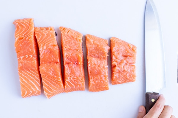 A large salmon filet cut into 5 portions on a white cutting board.