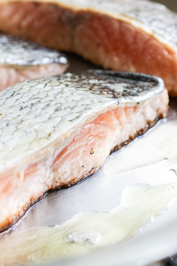 A raw salmon filet being seared in a stainless steel skillet.