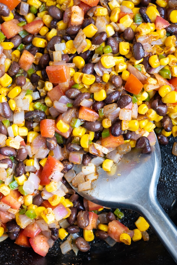 Black beans, corn, tomatoes, and onions, in a cast iron skillet for a Mexican recipe.