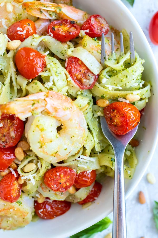 Shrimp Pesto Pasta recipe in a white bowl with some of the pasta wrapped around a metal fork.
