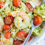 An easy pasta dinner recipe with pesto sauce, tomatoes, and shrimp.