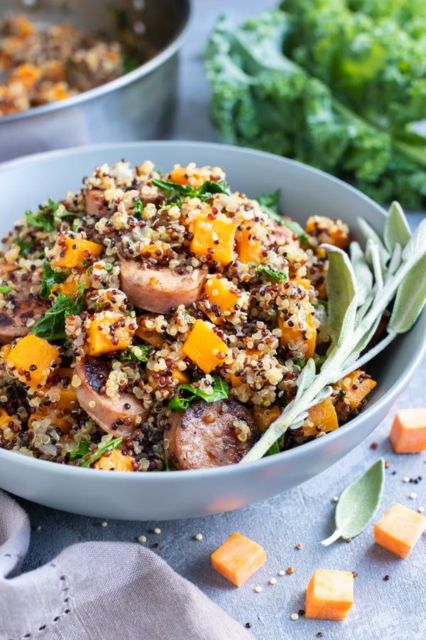 A grey bowl full of a quinoa, sausage, and sweet potato recipe with sage.