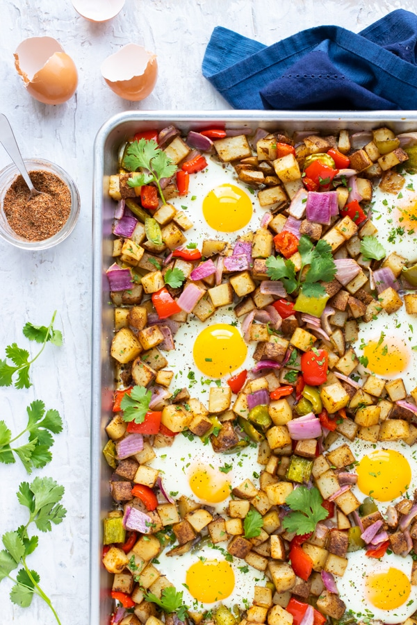 A sheet pan full of a breakfast potato hash recipe with over-easy eggs and blackened seasoning.