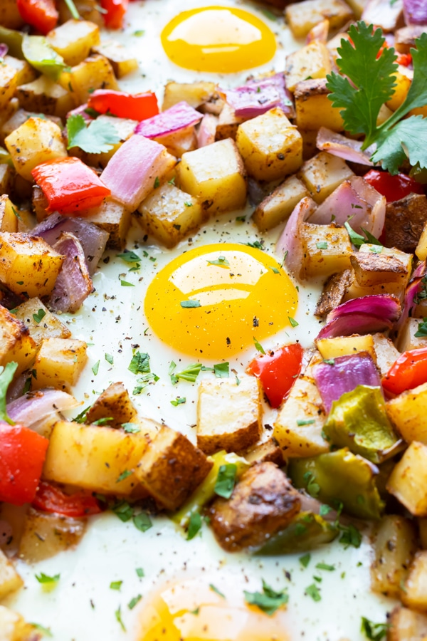 Three eggs surrounded by oven-roasted breakfast hash with red bell pepper and red onion.