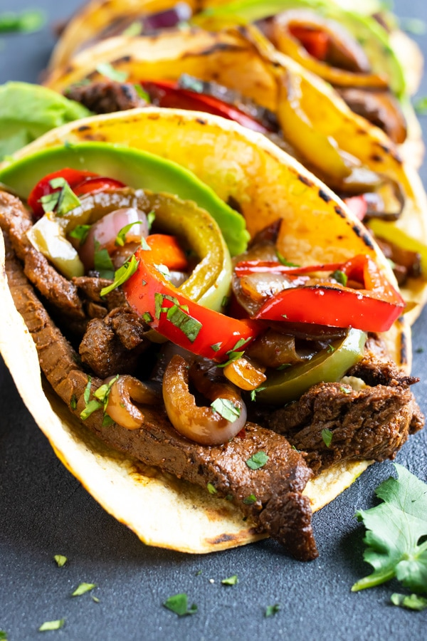 Seared steak fajitas with bell peppers and onions in a corn tortilla.