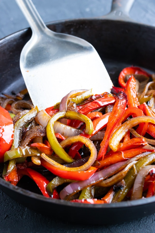 Sauteed vegetables for a fajita recipe in a cast-iron skillet.