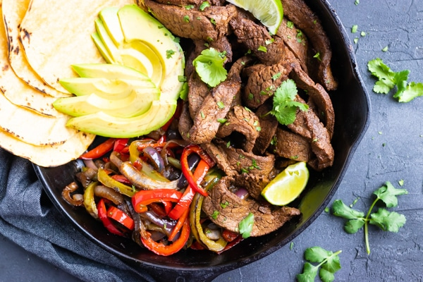 A black skillet full of flank steak fajitas, tortillas, and avocado.