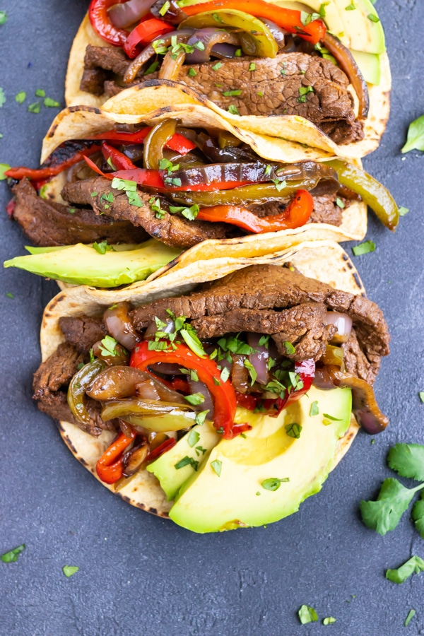 Steak fajita tacos with avocado in a row.