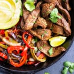 A large cast-iron skillet with an easy steak fajita recipe and vegetables.