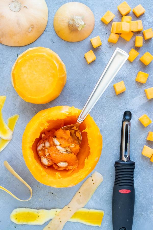 Peeled and cut butternut squash cubes next to a potato peeler.