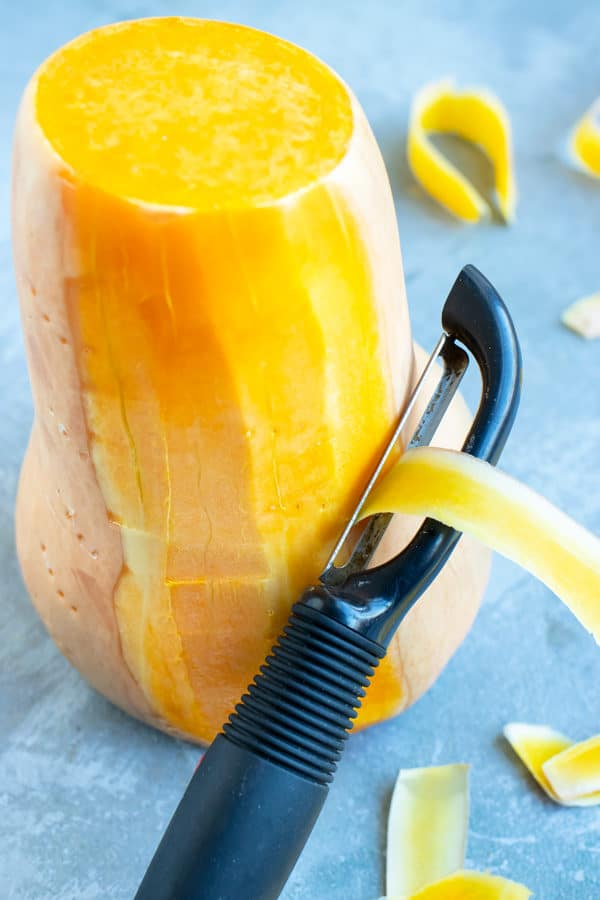 A potato peeler that is peeling the skin off of a large butternut winter squash.