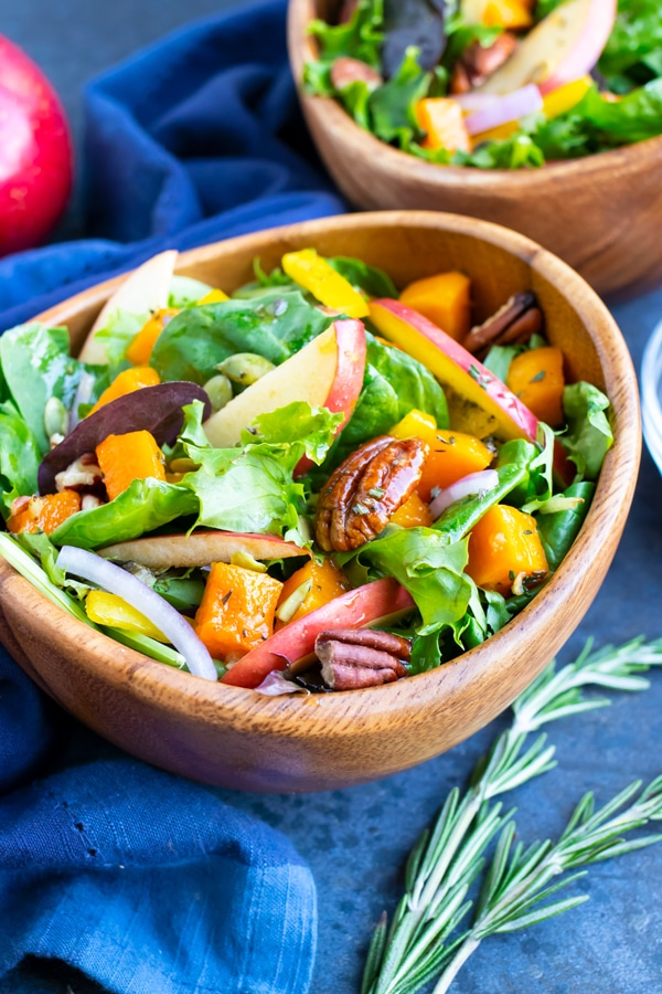 A wooden bowl full of a Fall harvest salad with apples, pecans, and an apple cider vinegar dressing.