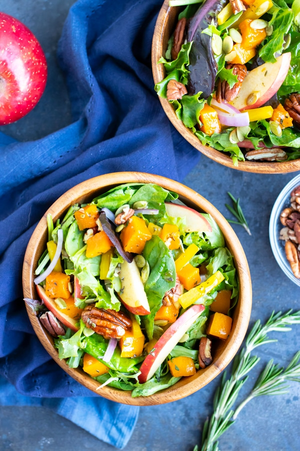 Two bowls full of a healthy, vegan, Fall harvest salad with apples and pecans.