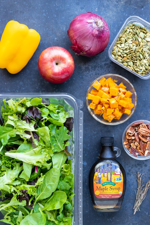 Mixed salad greens, apple, pumpkin seeds, pecans, bell pepper and onion as the ingredients in a Fall salad recipe.