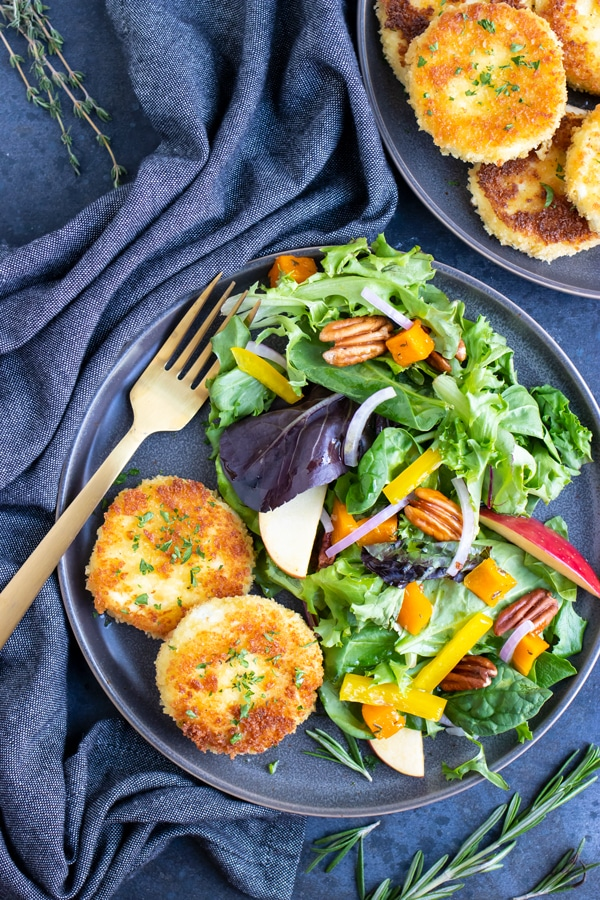 Two salads with honey herb goat cheese slices.