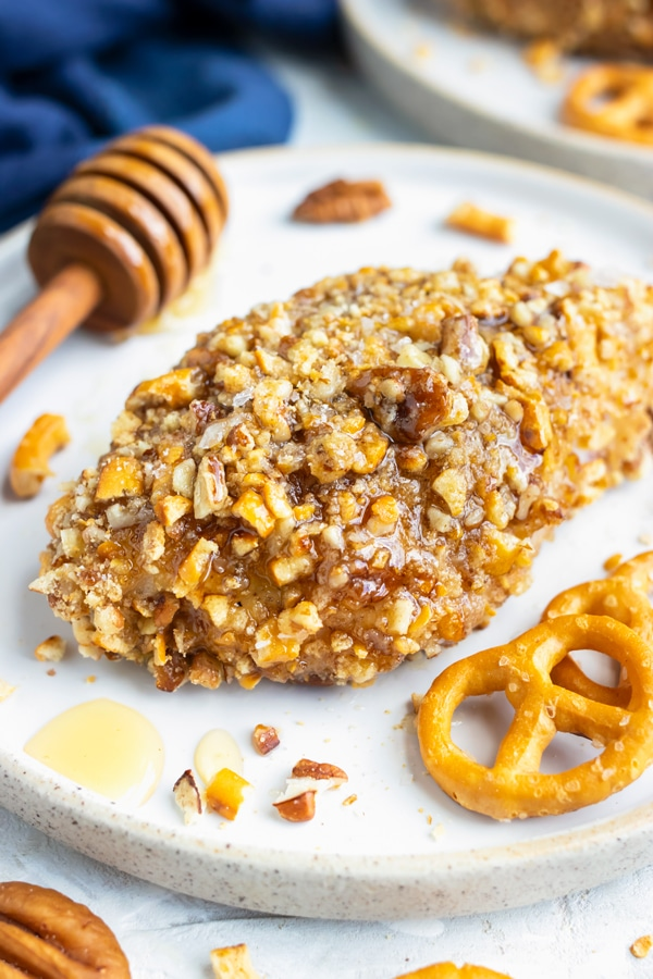 A healthy gluten-free honey baked chicken breast recipe on a white dinner plate next to pretzels and pecans.