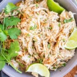 Shredded salsa chicken in a grey bowl with lime wedges and cilantro.