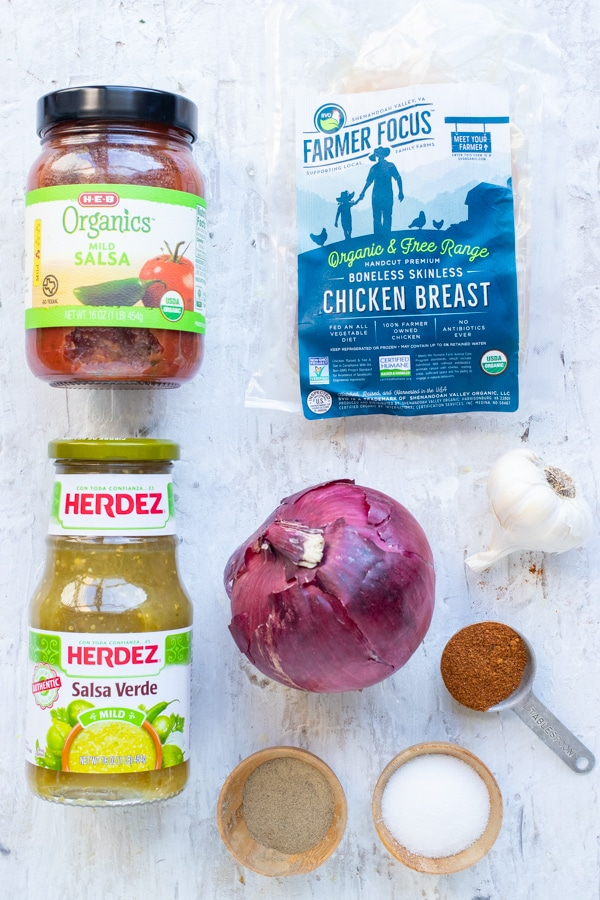 Salsa, onion, chicken breasts, red onion, and taco seasoning mix as the ingredients in an Instant Pot shredded salsa chicken recipe.