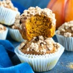 A big bite that has been taken out of a gluten-free pumpkin streusel muffin.